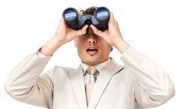 Surprised businessman looking through binoculars Stock Image