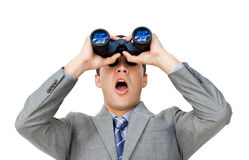 Surprised businessman looking through binoculars. Against a white background Royalty Free Stock Photo
