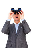 Surprised businessman looking through binoculars. Against a white background Royalty Free Stock Photography