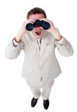 Surprised businessman looking through binoculars. Isolated on a white background Royalty Free Stock Images