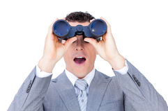 Surprised businessman looking through binoculars. Against a white background Royalty Free Stock Images