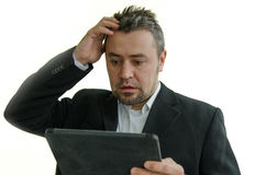Surprised businessman looking at tablet screen Stock Photo
