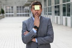 Surprised businessman with a note on his forehead royalty free stock photography