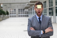 Surprised businessman with a note on his forehead stock image