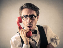 Surprised businessman at the phone stock photo