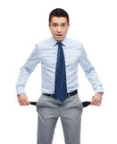 Surprised businessman showing empty pockets. Business, people, emotions, bankruptcy and failure concept - surprised businessman showing empty pockets Stock Image