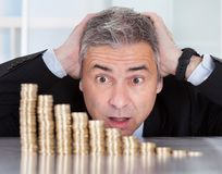 Surprised Businessman With Stack Of Coins. Shocked Mature Businessman Looking At Descending Stack Of Coins Royalty Free Stock Photo
