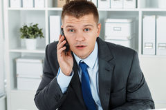 Surprised businessman. In suit sitting at working table in office an talking cellphone. Bewildered man solving problem remotely by phone conversation. Sudden Stock Photography