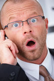 Surprised businessman talking on cellphone Stock Photography