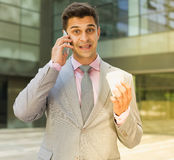 Surprised businessman talking on phone royalty free stock photography