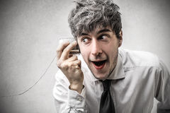Surprised businessman trying to listen to something. Young surprised businessman trying to listen to something through a metal glass Stock Images