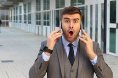 Surprised businessman with two cellphones stock image