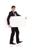 Surprised businessman walks with placard. Royalty Free Stock Photos