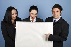 Surprised businesspeople with blank sign. Three people business team holding a blank billboard and the businessman pointing to copy space while the females Stock Photography