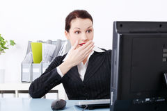 Surprised businesswoman. Surprised beautiful caucasian businesswoman looking at the computer and sitting behind the desk in the office Stock Photo