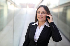 Surprised businesswoman. A surprised business woman is talking on the phone in front of a corporate building Stock Image