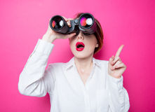 Surprised businesswoman with binoculars. Beautiful red-haired surprised businesswoman with binoculars on pink background Royalty Free Stock Images