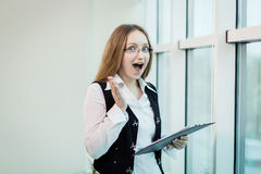 Surprised businesswoman with document.Amazed businesswoman screa Royalty Free Stock Photos