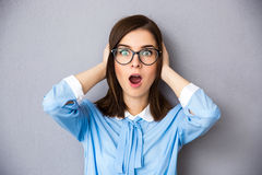 Surprised businesswoman with glasses over gray background Stock Photo