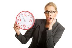 Surprised businesswoman holding a big clock Stock Images