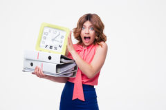 Surprised businesswoman holding clock and folders Stock Photo