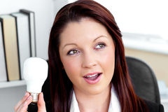 Surprised businesswoman holding a light bulb Royalty Free Stock Photos