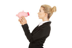 Surprised businesswoman holding a piggybank Stock Images