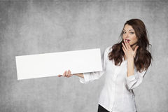 Surprised businesswoman holds a place for your advertisement Stock Image