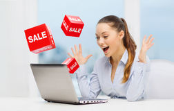 Surprised businesswoman with laptop and sale signs. Business, people, technology and shopping concept - surprised businesswoman typing on laptop computer with Stock Photography