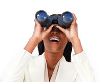 Surprised businesswoman looking through binoculars Stock Images