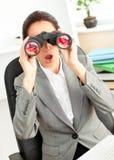 Surprised businesswoman looking through binoculars Stock Image