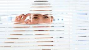 Surprised businesswoman peeking through the blinds