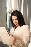 Surprised businesswoman reading journal Royalty Free Stock Images