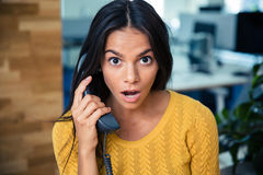Surprised businesswoman talking on the phone Stock Image
