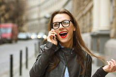 Surprised businesswoman walking down the street while talking on Stock Photo