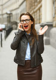 Surprised businesswoman walking down the street while talking on Stock Photos