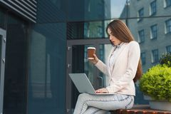 Caucasian businesswoman working with laptop outdoors Royalty Free Stock Photos