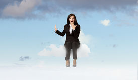 Surprised businesswoman. Young emotional businesswoman sitting on cloud above city Stock Image