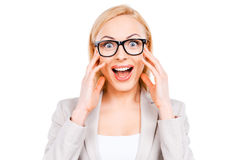 Surprised businesswoman. Surprised young businesswoman staring at camera while standing against white background Royalty Free Stock Image