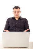 Surprised casual man with glasses looking at laptop Royalty Free Stock Photos
