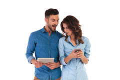 Surprised casual man showing good news to girlfriend on tablet Stock Photo