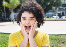Surprised caucasian girl with curly black hair. Outdoor in a city in south america in the summer Stock Photo