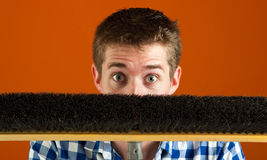 Surprised Caucasian Male Hiding Behind Broom Stock Image