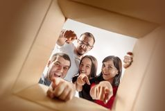The people unpacking and opening carton box and looking inside stock photography