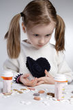 Surprised child. Surprised little girl, looking at pile of medications Royalty Free Stock Photo