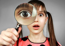 Surprised child girl, searching with magnifying glass royalty free stock images