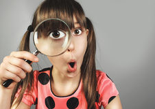 Surprised child girl, searching with magnifying glass. Surprised little girl, searching with magnifying glass stock photos