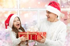 Surprised child with her father holding a gift. Portrait of a surprised little girl with her father holding a big red gift box Royalty Free Stock Photography