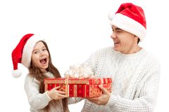 Surprised child with her father holding a gift. Portrait of a surprised little girl with her father holding big red gift box Stock Photos