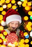 Surprised child holding Christmas gift box Stock Photos